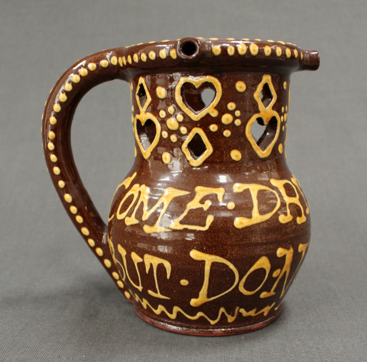 A glazed terracotta puzzle jug