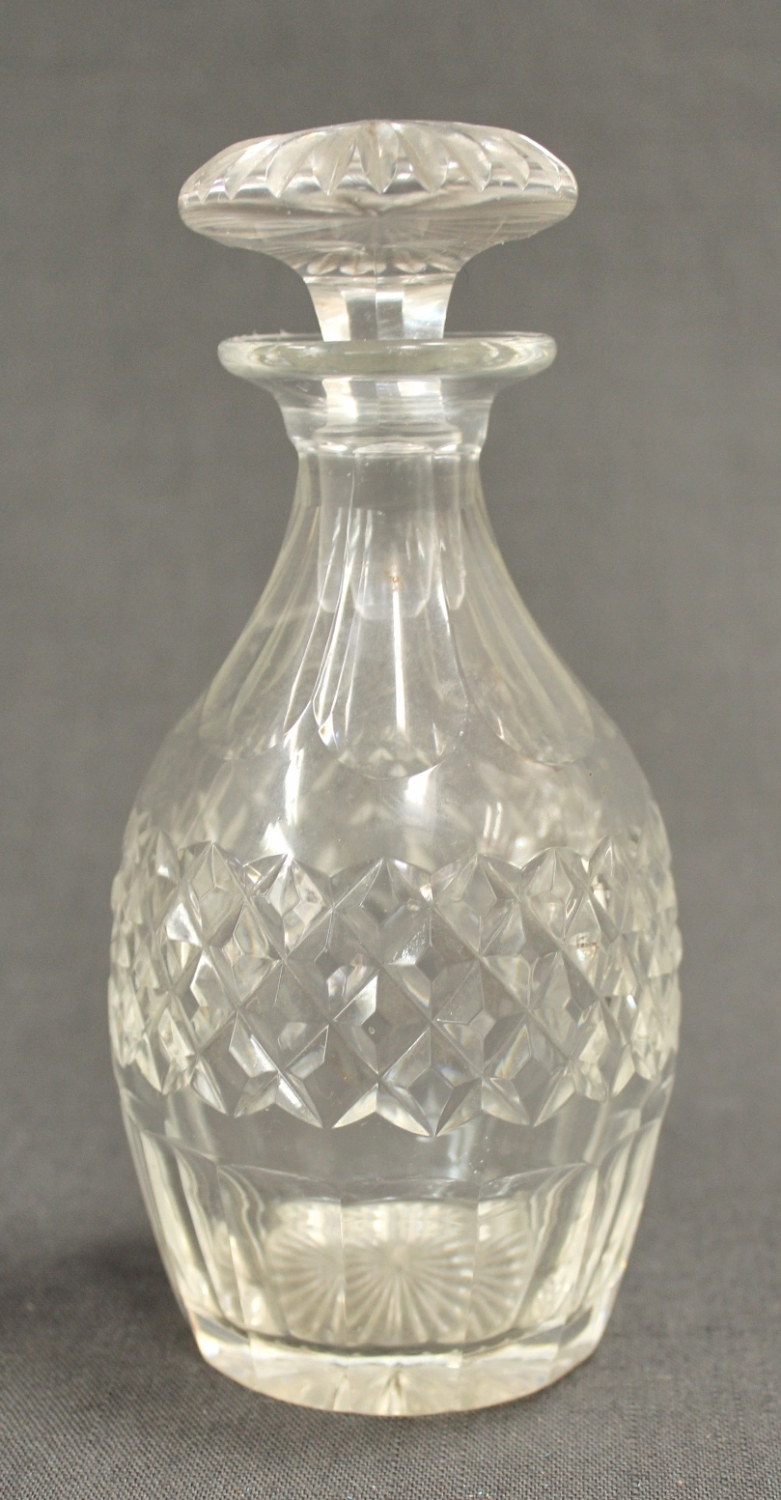 An ovoid clear glass liqueur decanter