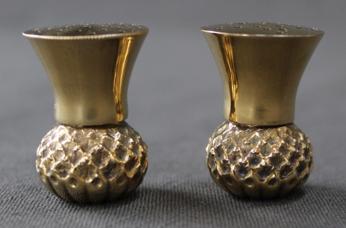 A pair of silver-gilt thistle pepperettes