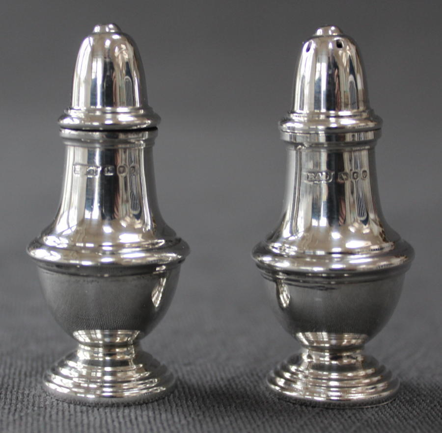 A pair of silver vase shaped cruets