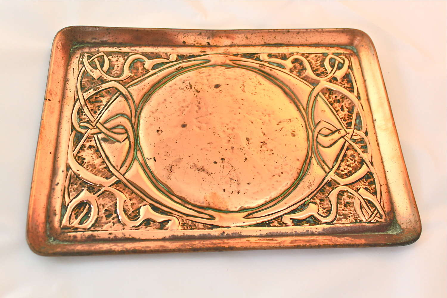 An Arts & Crafts embossed copper tray